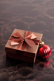 Brown gift box and Christmas ball on black background, closeup Royalty Free Stock Photo