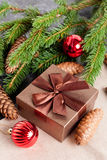Brown gift box, Christmas ball and Green fir branches Stock Photo