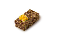 Gift. Brown gift box with gold bow on white background Royalty Free Stock Photo