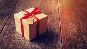 Brown gift box and red ribbon with tag on wood background with s. Pace Stock Photography