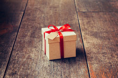 Brown gift box and red ribbon with tag on wood background with s. Pace. Vintage gift box on wood Royalty Free Stock Image