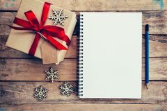 Brown gift box, snowflakes and notebook on wood table for christ Stock Photo