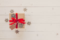Brown gift box and snowflakes on white wooden background. Vintag Royalty Free Stock Images