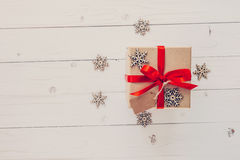 Brown gift box and snowflakes on white wooden background. Vintag Royalty Free Stock Image