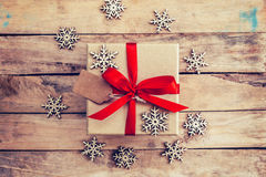 Brown gift box and snowflakes on wooden background. Vintage gift Stock Photography