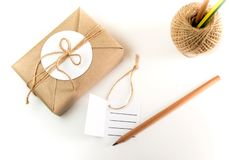 Gift box wrapped in kraft paper and rustic hemp as natural rusti. Brown gift box wrapped in kraft paper and rustic hemp cord spool as natural rustic style with stock photo