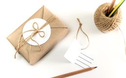 Gift box wrapped in kraft paper and rustic hemp as natural rusti. Brown gift box wrapped in kraft paper and rustic hemp cord spool as natural rustic style with stock photography