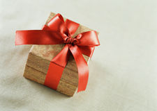 A brown gift with a red satin ribbon and a bow Royalty Free Stock Photos