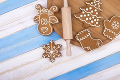 Brown gingerbread on the board. Gingerbread, rolling pin and board on striped background. Preparation of holiday sweets royalty free stock image
