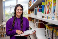 Brown smiling girl with glasses and pigtails consults a book in a library stock photography
