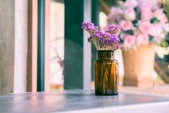 Brown-Glasflasche mit getrocknetem Rosa und purpurrote Blume auf Tabelle herein stockfotos