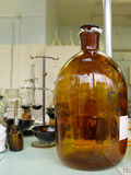 Brown glass. Huge brown glass bottle in a drugstore near to other equipment Stock Photography