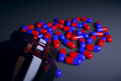 Brown glass bottle with red and blue pills Royalty Free Stock Photos