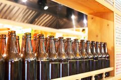Brown glass bottles of beer in row on wooden shelf, bar interior design, beer tasting concept, nightlife style, brewery production. Brown glass bottles of beer royalty free stock images