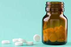 Brown glass pills bottle and round pills Royalty Free Stock Photography