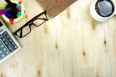 Brown glasses and financial calculator, cup of coffee on blank w. Ood background. Working office table topview royalty free stock photo