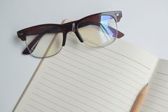Brown glasses placed on the notebook and pencil,copy space royalty free stock images