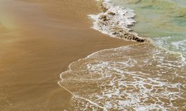 Brown/Golden beach with small waves. Near Puerto Plata in the Dominican Republic stock photography