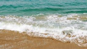 Brown/goldener Strand mit kleinen Wellen stockfotos