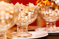 Brown gomółki cukierki w pucharach na stole i cukier, zbliżenie, selekcyjna ostrość, grżemy brzmienie fotografia royalty free