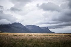 Brown Grass Field and Gray Mountains Under Gray Clouds stock images