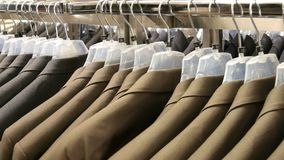 Brown and gray men`s jackets hang on hangers in the men`s clothing store in the mall. A huge range of men`s suits on. Hangers in the shopping center stock video footage