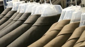 Brown and gray men`s jackets hang on hangers in the men`s clothing store in the mall. A huge range of men`s suits on. Hangers in the shopping center close up stock footage