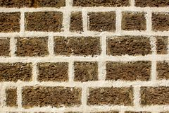 Brown gray wall of porous volcanic stone blocks with white cement. rough surface texture. A brown gray wall of porous volcanic stone blocks with white cement stock image