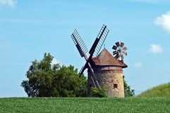 Brown and Gray Windmill Beside Green Tree Under Blue Cloudy Sky during Day Time Royalty Free Stock Photo