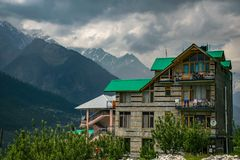 Brown and Green Concrete Building Near Mountains at Daytime royalty free stock photo
