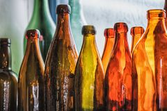 Brown and green old glass bottles on windowsill, with curtain. Closeup, daylight Stock Images