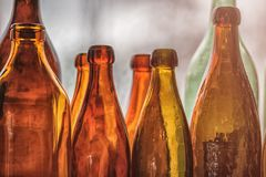 Brown and green old glass bottles on windowsill, with curtain. Closeup, daylight Royalty Free Stock Photography