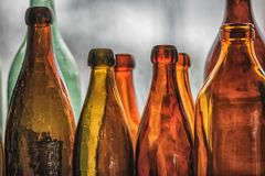 Brown and green old glass bottles on windowsill, with curtain. Closeup, daylight Stock Photo