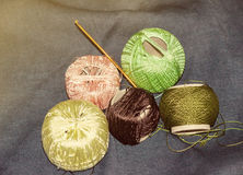 Brown, green and pink tangles for knitting on a denim background Royalty Free Stock Images