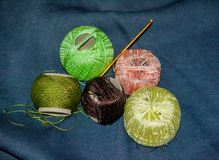 Brown, green and pink tangles for knitting on a denim background Stock Image