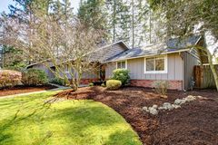 Brown grey house exterior with spring landscape. Stock Photo