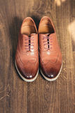 Brown grooms wedding shoes on wooden background Stock Image