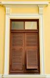 Brown-hölzerne Blendenverschlüsse auf der gelben Wand Stockfotografie