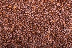 Brown ha arrostito i chicchi di caffè vicino su struttura Immagine Stock