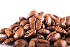 Brown ha arrostito i chicchi di caffè vicino su su fondo bianco Immagini Stock
