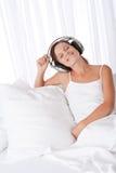 Brown-Haarfrau mit den Kopfhörern, die auf Sofa sitzen Stockfoto