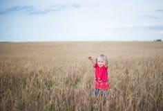 Brown-Haarmädchen, das auf dem Roggengebiet spielt Stockfoto