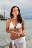 Brown hair fashion model in bikini by the sea Royalty Free Stock Image