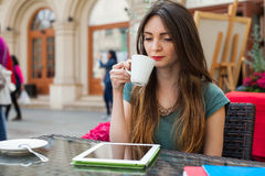 Brown hair girl sitting behind table in café restaurant, drinki Royalty Free Stock Photography