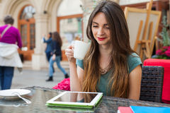 Brown hair girl sitting behind table in café restaurant, drinki Royalty Free Stock Photo