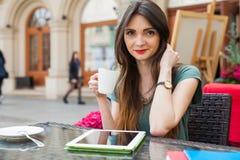 Brown hair girl sitting behind table in café restaurant, drinki Stock Photo