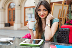 Brown hair girl sitting behind table in café restaurant, drinki Stock Photo