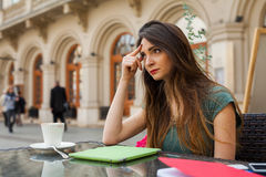 Brown hair girl sitting behind table in café restaurant. She is Stock Photography