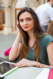 Brown hair girl sitting behind table in café restaurant and smi Royalty Free Stock Photography