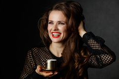 With brown hair holding cup of coffee on dark background Stock Photos